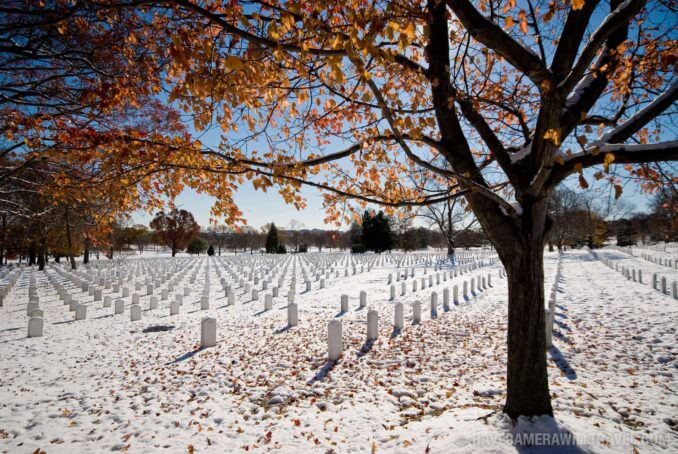 Arlington National Cemetery in the snow with fall foliage