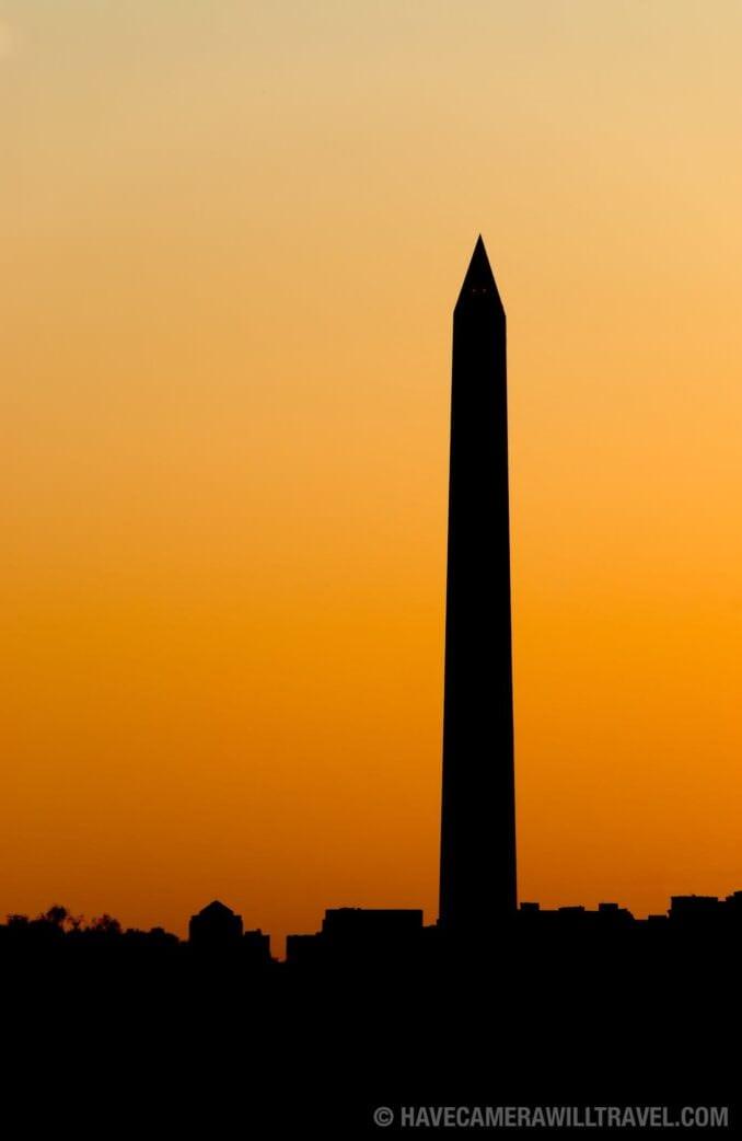 Washington Monument at dusk against golden glow of sunset